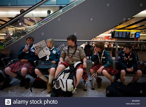 Wearing kilts, boys from a Scottish scout group sit and in